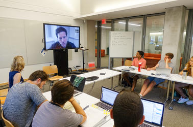 Heather Klemann and several students watch a television screen to interview an expert via ZOOM