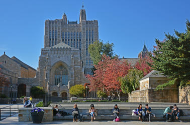 Students sit on a bench outside of Sterling Memorial Library