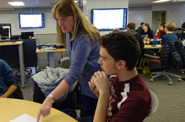 Helen Caines helping a student learn in TEAL classroom