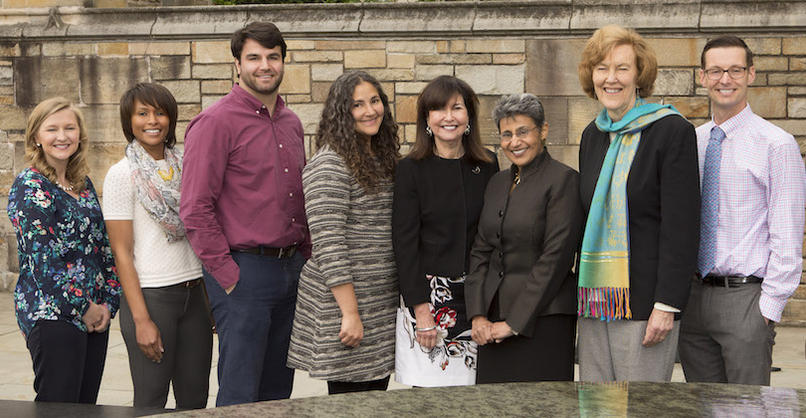 Eight people stand behind the Women's Table memorial in front of SML