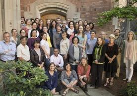 A group of 55 Yale faculty and staff members standing in the courtyard at the Hall of Graduate Studies