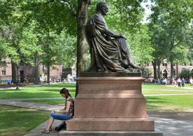 A person rests during Freshmen move-on on a statue in Old Campus at Yale